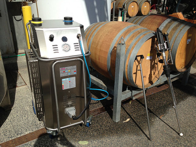 the bacchus steam generator is shown with a wine barrel set up for clening, and two steam diffusers- a single head model, as well as a rotating-head diffuser