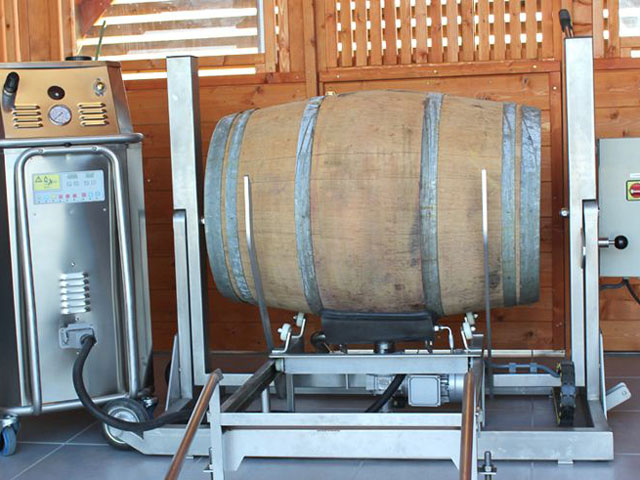 wine barrel ready for sanitizing, rests on a stand with bacchus steam pressure machine alongside